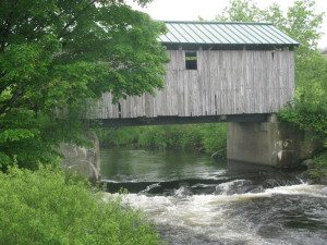 Covered bridge over swollen river near Rankin dairy farm